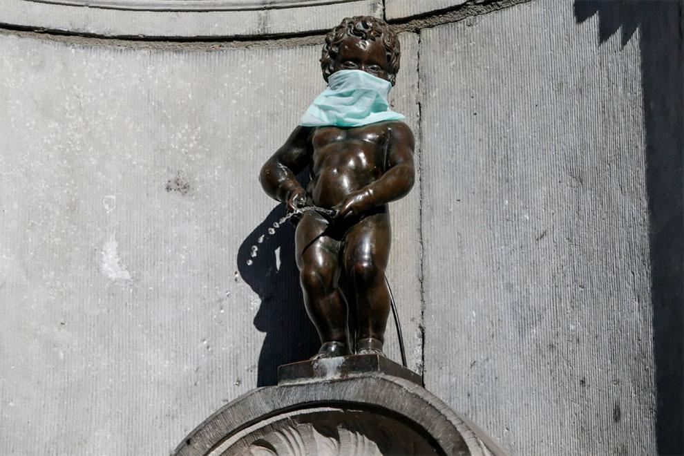 """A famosa estátua do """"Menino Fazendo Xixi"""" (Manneken-Pis) em Bruxelas, usando máscara protetiva em suporte aos médicos batalhando contra o Corona Virus COVID-19"""
